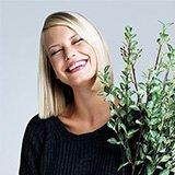 Lachende Frau hält Pflanze